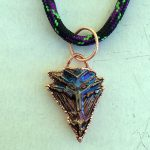Tiny bismuth arrowhead pendant.